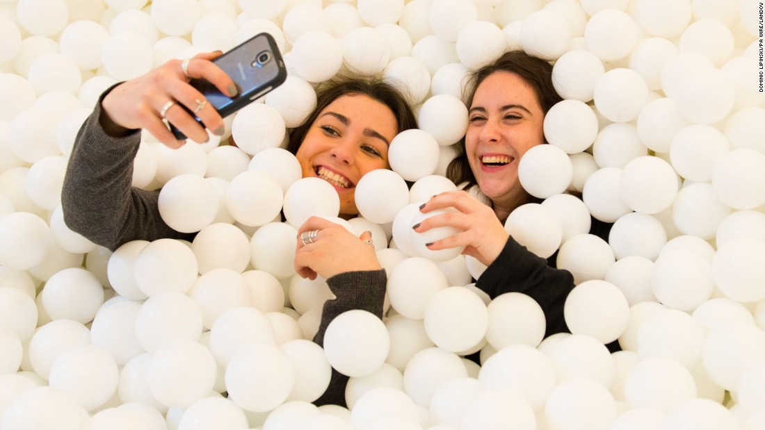 "Visitors of ""Jump In!"" take photos inside the adults-only ball pit Wednesday, February 4, in London. The installation, which held more than 80,000 white balls, was at the Pearlfisher design agency."