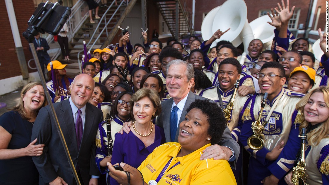 Former U.S. President George W. Bush and his wife, Laura, pose for a selfie with members of a high school band in New Orleans on Friday, August 28.