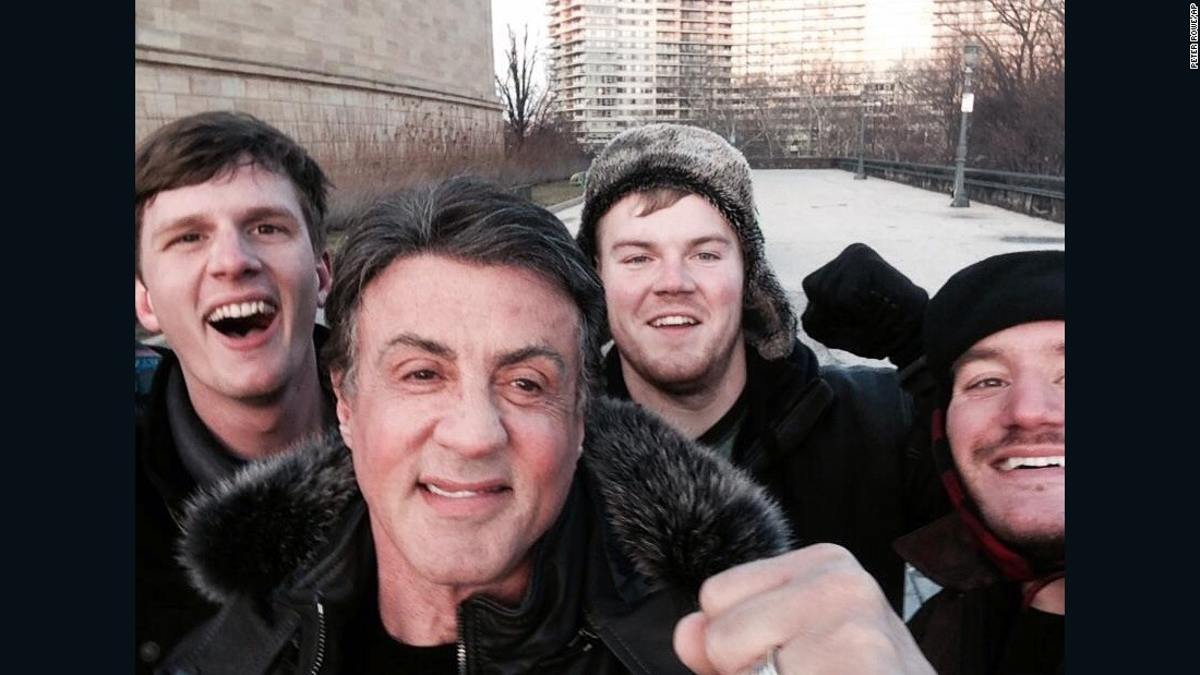 "Peter Rowe, right, takes a selfie with friends Jacob Kerstan, left, Andrew Wright, third from left, and actor Sylvester Stallone in Philadelphia on Saturday, January 17. Rowe said the three friends had just finished racing up the steps at the city's Museum of Art, where Stallone filmed the classic training scene in ""Rocky,"" and discovered the actor at the top of the steps."