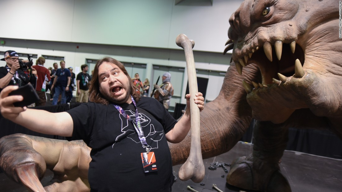 "A ""Star Wars"" fan takes a selfie with a rancor exhibit at a fan experience in Anaheim, California, on Thursday, April 16."