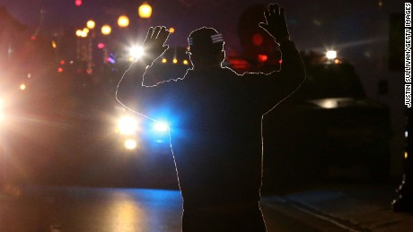 FERGUSON, MO - NOVEMBER 24:  A protestor stands in front of police vehicles with his hands up during a demonstration on November 24, 2014 in Ferguson, Missouri. A St. Louis County grand jury has decided to not indict Ferguson police Officer Darren Wilson in the shooting of Michael Brown that sparked riots in Ferguson, Missouri in August.  (Photo by Justin Sullivan/Getty Images)