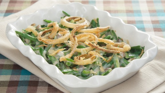 The only green vegetable at many Thanksgiving dinners, a three-quarter cup serving of green bean casserole contains 230 calories. The cream of mushroom soup, milk and crispy, fried onions in the casserole version drive up the calories.  Another version, green beans that are topped with grated Parmesan cheese, has about 50 calories.