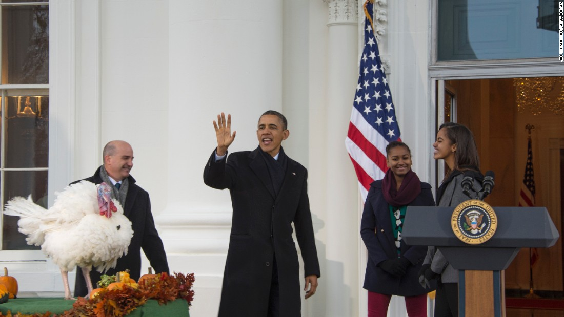 Obama waves after pardoning the 2013 national Thanksgiving turkey, Popcorn, with daughters Sasha and Malia and National Turkey Federation Chairman John Burkel.