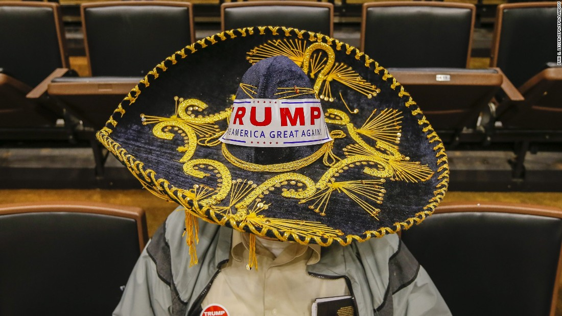 Jim Yates wears a Mexican sombrero sporting a bumper sticker while waiting for Donald Trump to arrive for a campaign town hall event at Wofford College in Spartanburg, South Carolina, on Friday, November 20.