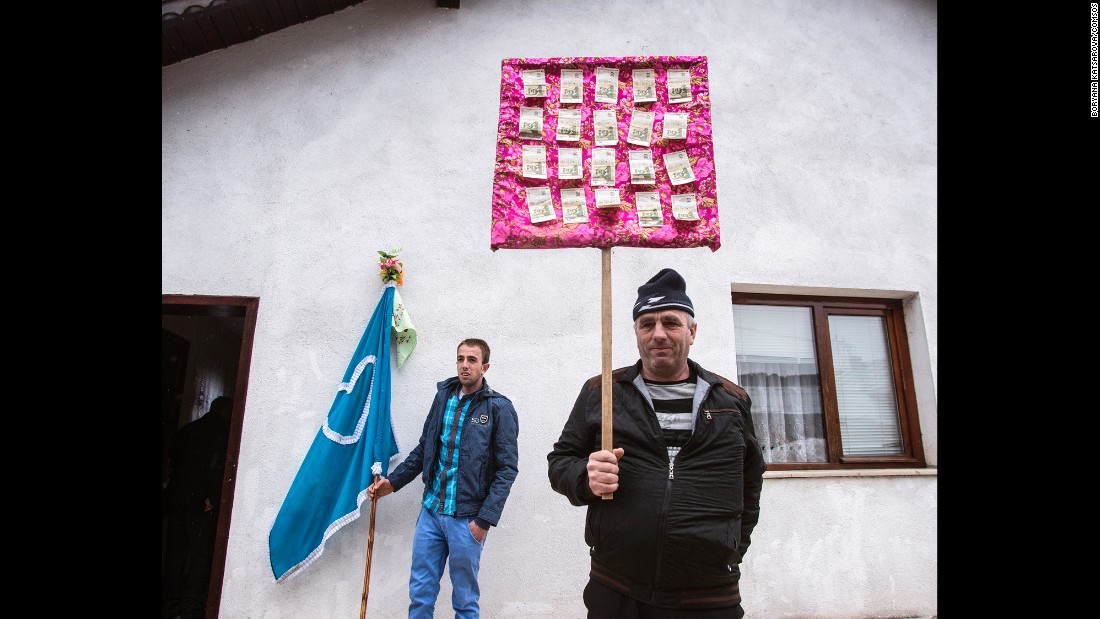 Relatives are seen in front of the house of Robova's fiance, Refat Atipov. They are holding some of the gifts prepared from his family for his future wife and her family.