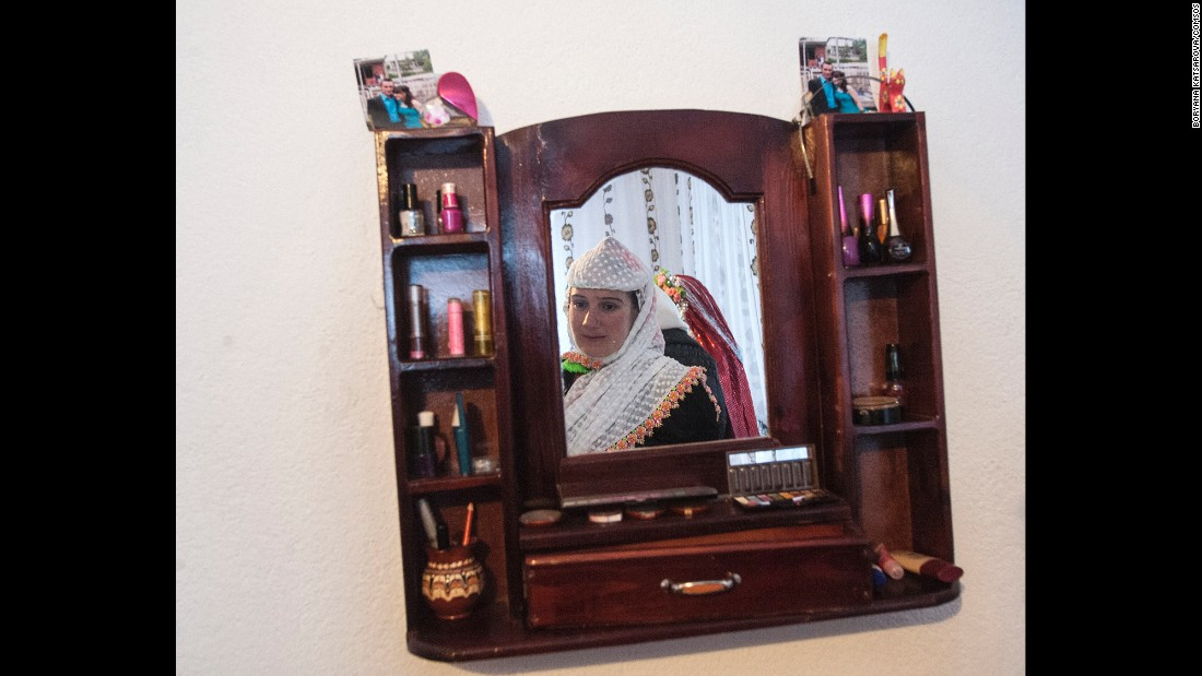 One of Robova's relatives is seen in a mirror while the bride's traditional makeup is applied.