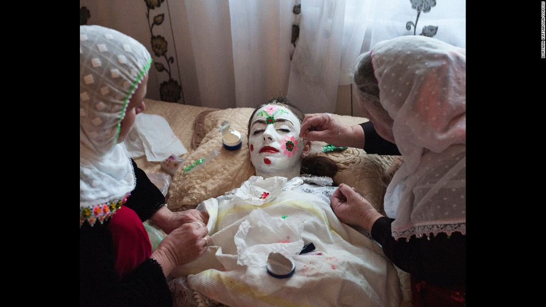 "Robova is dressed in traditional garments and elaborate face paint called ""gelina."" The face-painting process, a symbol of the bride's purity, can take up to two hours. It is considered a specialized art."