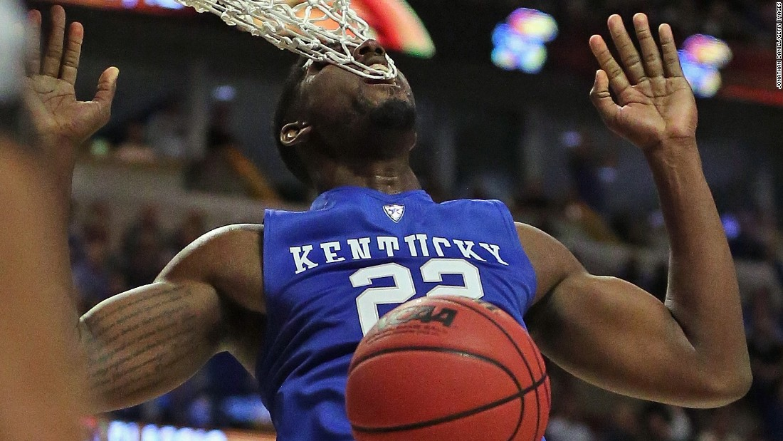 Kentucky's Alex Poythress gets his teeth caught in the net after dunking against Duke in Chicago on Tuesday, November 17.