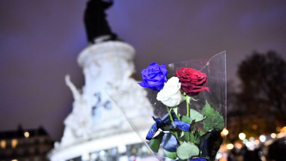 A man holds roses in the colors of the French national flag at Place de la Republique (Republic Square) in Paris on November 21, 2015 as he arrives to pay tribute to the victims of the November 13 terror attacks. A coordinated wave of attacks on Parisian nightspots claimed by Islamic State group (IS) jihadists killed 130 people.