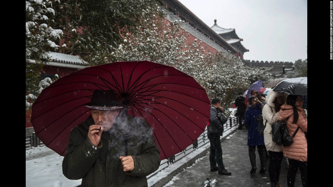 A man smokes as he shields himself from the snow outside the Forbidden City in Beijing.