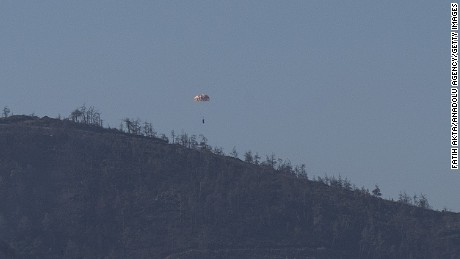 HATAY, TURKEY - NOVEMBER 24: A person parachutes out of a warplane which went down in Syria's northwestern Turkmen town of Bayirbucak near Turkeys border on November 24, 2015. It remains unclear to which country the aircraft belongs to. (Photo by Fatih Akta/Anadolu Agency/Getty Images)