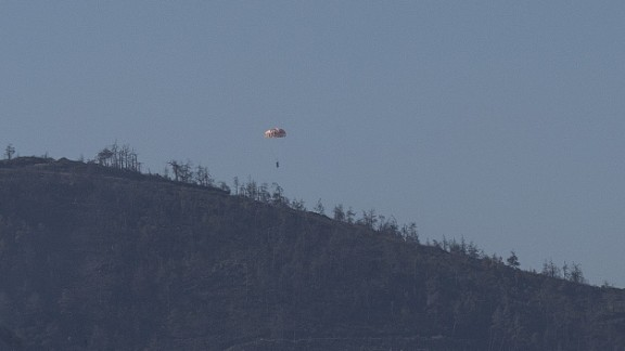 A Russian airman descends from the downed jet via parachute.