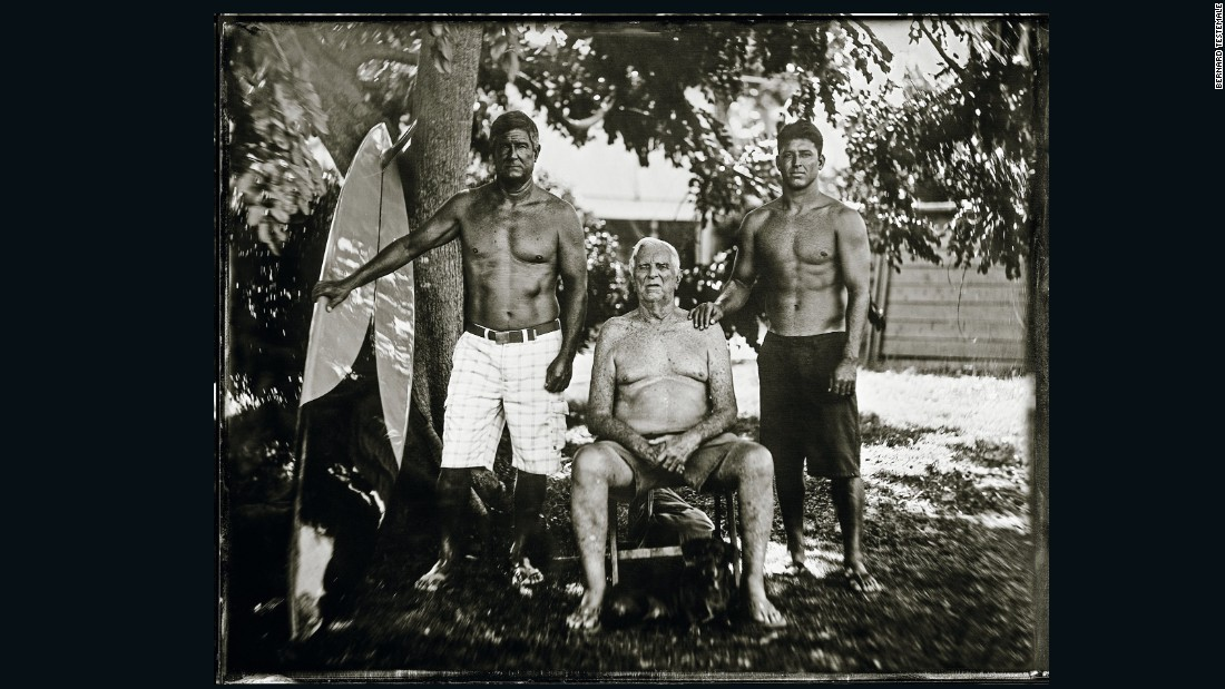 "George Downing (seated) is a Hawaiian surfing pioneer, and is the longtime contest director for ""the Eddie"" -- he decides if the event will take place.<br />His son Keone Downing (left) won the contest in 1989-90, riding a board shaped by his dad. Keone's son Kaohi (right) also surfs, and at one stage played minor league baseball."
