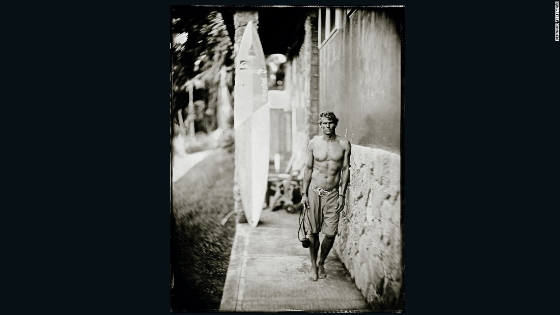 "The Australian is one of 27 surfers invited to the 2015-16 Aikau event at Waimea Bay. For this image, he is leaning against the wall in order to keep still, as the wet-plate process requires subjects to pose in place for up to five seconds, says Testemale.  <br />""It's a really slow process because the sensitivity of the wet plate is really, really low, like one ISO (light sensitivity rating) or less. You cannot just click and get a picture, you have to be steady."""