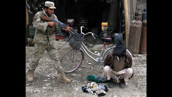 January 20: An Afghan security officer aims his weapon at a man who was allegedly planning a suicide bomb attack in Jalalabad, Afghanistan.