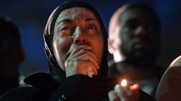 February 11: A woman cries during a vigil as she sees photos of the three people who were killed at an apartment near the University of North Carolina at Chapel Hill. Three Muslim students -- Deah Shaddy Barakat, 23; his wife, Yusor Mohammad, 21; and her sister, Razan Mohammad Abu-Salha, 19 -- were found shot to death a day earlier. A 46-year-old suspect, Craig Stephen Hicks, was charged with murder.