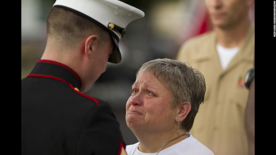 "<strong>July 21: </strong>Cathy Wells, mother of Lance Cpl. Squire K. ""Skip"" Wells, is given flowers by a U.S. Marine at her son's vigil in Marietta, Georgia. Wells, a 21-year-old reservist, was one of five service members killed during <a href=""http://www.cnn.com/2015/07/16/us/gallery/chattanooga-tennessee-shooting/index.html"" target=""_blank"">a shooting at a Navy reserve center</a> in Chattanooga, Tennessee. The shooter, Mohammad Abdulazeez, died in a gunfight with law enforcement. He had also shot up a military recruiting center before driving to the reserve center."