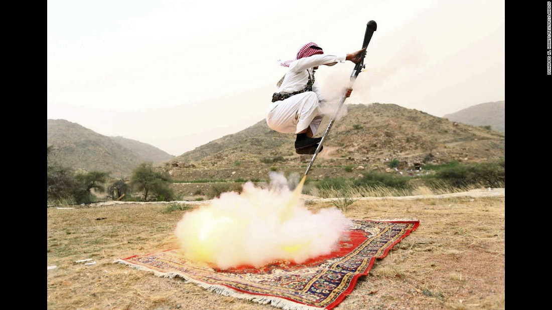 <strong>August 8:</strong> A man fires a weapon as he dances during a traditional celebration near Taif, Saudi Arabia.