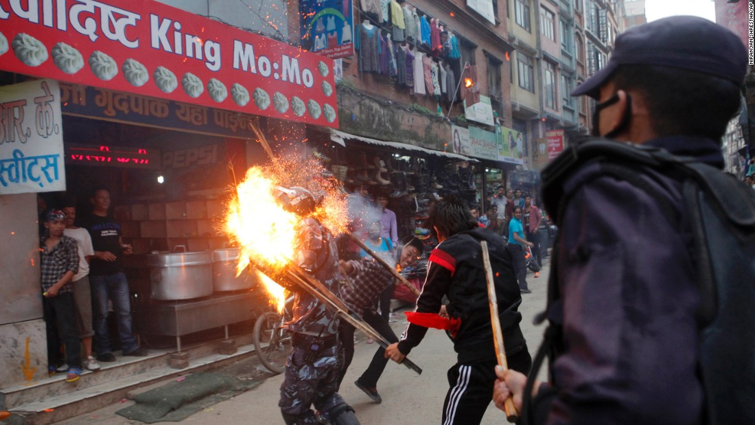 "<strong>August 15:</strong> Protesters hit a police officer with a torch during a rally in Kathmandu, Nepal. There were <a href=""http://www.cnn.com/2015/08/25/asia/nepal-police-protester-deaths/"" target=""_blank"">violent clashes</a> over the country's <a href=""http://www.cnn.com/2015/09/20/asia/nepal-new-constitution-explainer/"" target=""_blank"">proposals for a new constitution,</a> and some police officers were killed or injured. The officer in this photo was injured, according to the photographer, but he survived."