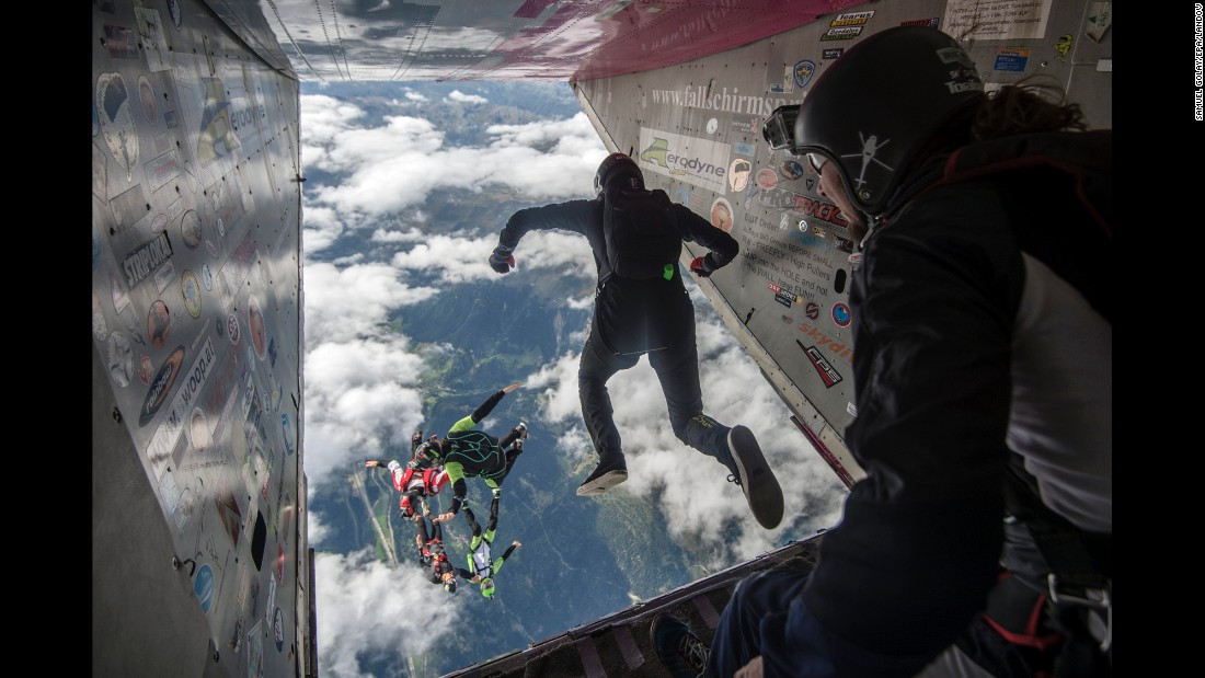 <strong>August 27:</strong> People jump out of a plane during the Mountain Gravity skydiving competition in Quinto, Switzerland.