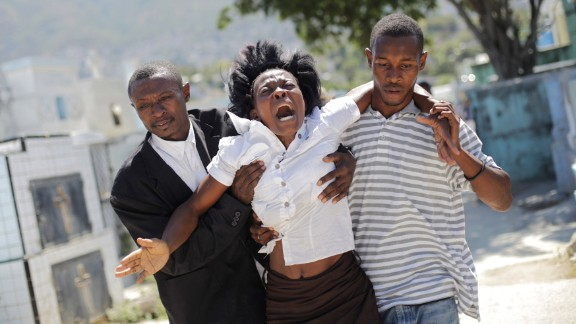 February 21: A woman reacts as she walks to a cemetery to attend the funeral of Carnival stampede victims in Port-au-Prince, Haiti. At least 16 people were killed during an accident involving an electrical shock on a float, government officials said. Video from the scene appeared to show a power line striking a man atop a float. Chaos erupted, and revelers ran in all directions. Officials canceled Carnival activities and declared three days of national mourning.