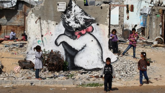 February 26: Children stand next to a Banksy mural on the remains of a destroyed house in Beit Hanoun, Gaza. The house was destroyed last year during fighting between Israel and Hamas. See more work from Banksy, the anonymous street artist