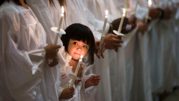 April 4: Jillian Nguyen, 3, stands with others as they are baptized into the Catholic faith in Philadelphia.