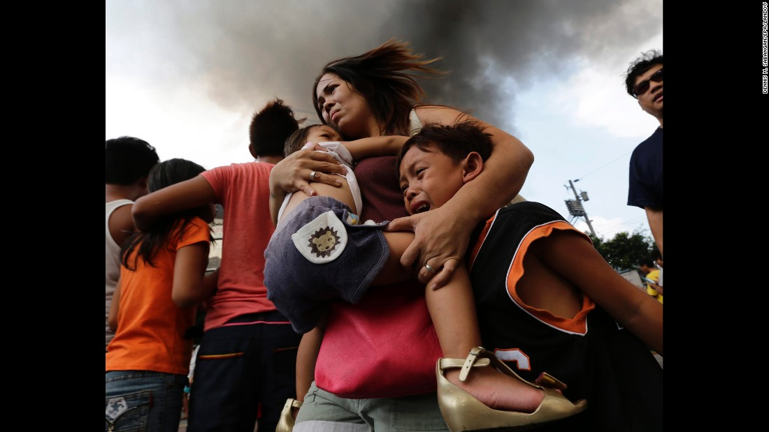 <strong>April 29:</strong> A mother carries her children while their house burns at a residential slum area in Manila, Philippines. The Manila Fire Department said the fire left more than 30 families homeless.