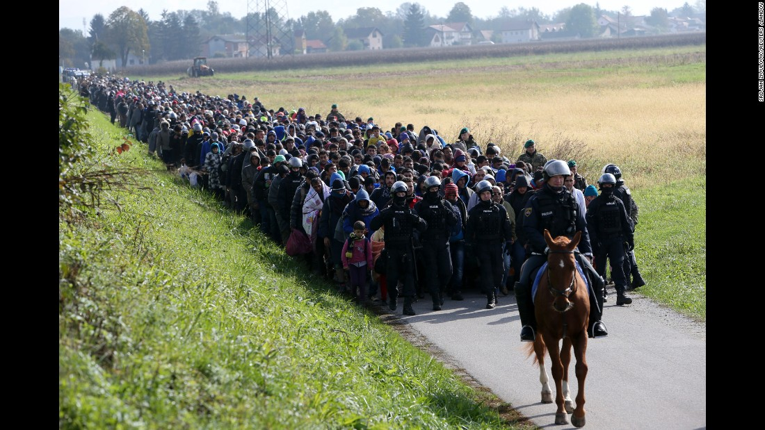 <strong>October 20:</strong> A mounted police officer leads a group of migrants near Dobova, Slovenia. Thousands of migrants flooded into the country from Croatia after Hungary sealed off its border.