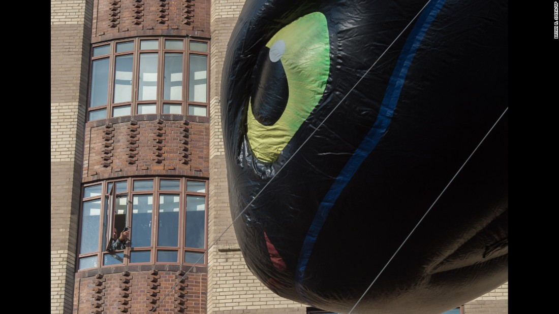"A spectator takes a photo of the balloon Toothless as it floats past. Toothless is a character from the animated movie ""How to Train Your Dragon."""