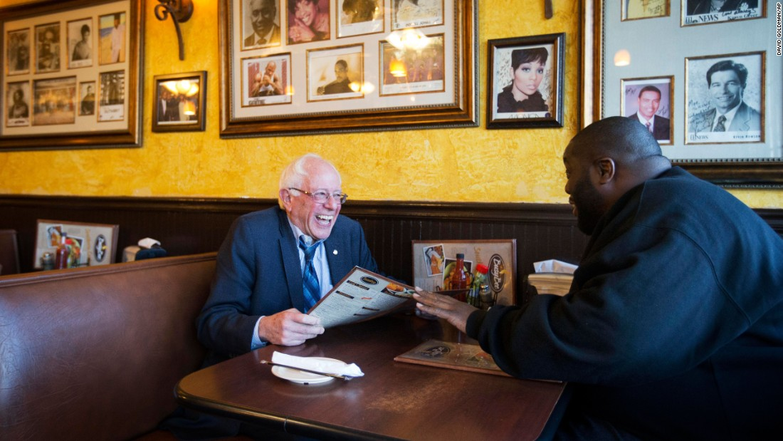 U.S. Sen. Bernie Sanders, who is seeking the Democratic Party's nomination for President, sits at an Atlanta cafe with rapper Killer Mike, right, on Monday, November 23. The rapper introduced Sanders at a campaign event later in the evening.