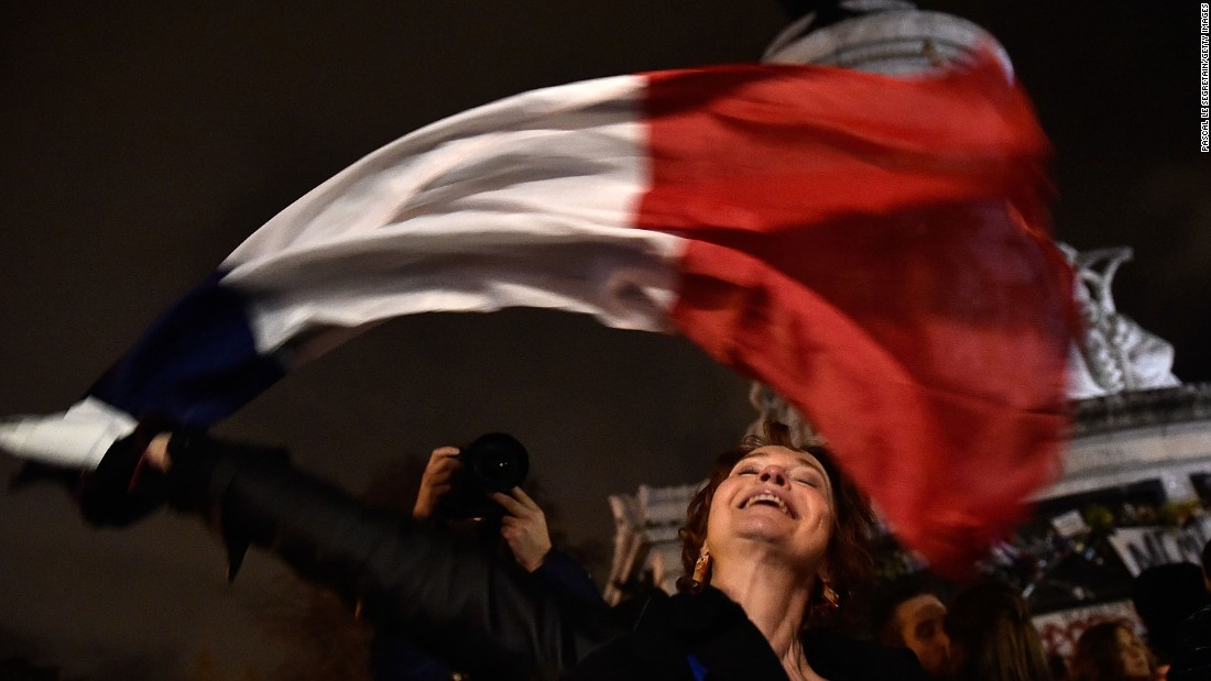 "A woman waves a French flag in Paris on Friday, November 20. A week earlier,<a href=""http://www.cnn.com/2015/11/13/world/gallery/paris-attacks/index.html"" target=""_blank""> a series of terrorist attacks</a> killed 130 people and injured hundreds more in the French capital."