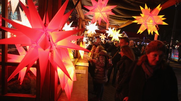 Visitors walk past a stall selling illuminated stars at the annual Christmas market at Alexanderplatz in Berlin.