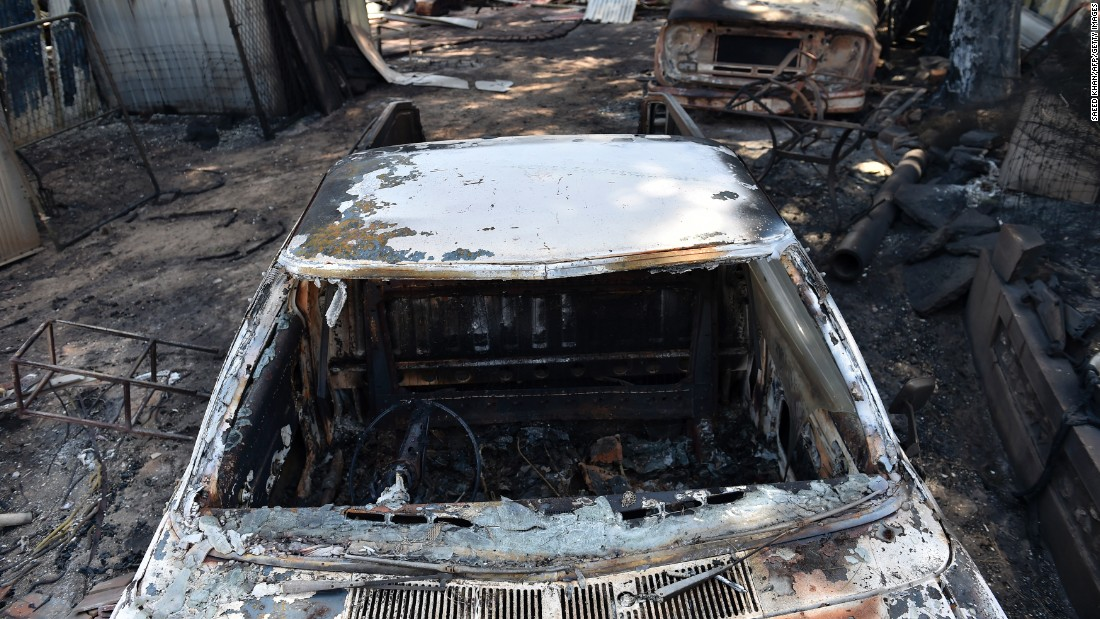 A burnt-out vehicle sits on a similarly ravaged property in Freeling on November 26. More than 13 people have been hospitalized as a result of the raging fire, some in a critical condition.