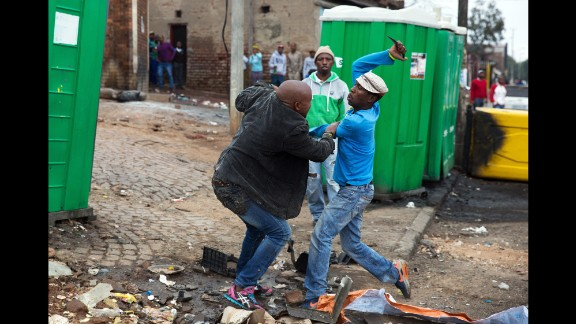 April 18: Mozambican Emmanuel Sithole, left, was walking down a street in Johannesburg's Alexandra Township when four men surrounded him. Sit