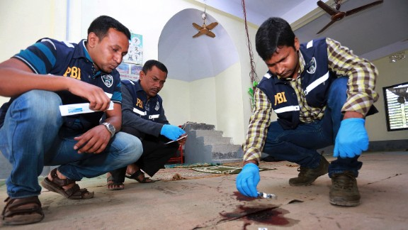 Investigators check the scene of a mosque attack Friday, November 27, in northern Bangladesh