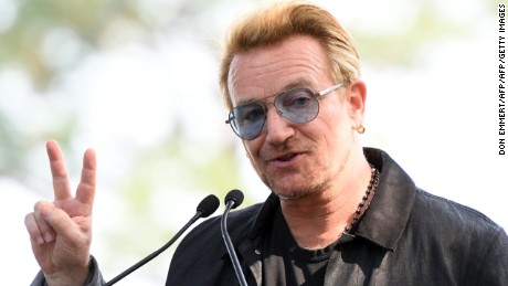 Bono holds up a peace sign during a dedication ceremony for a giant tapestry, from Amnesty International, in honor of John Lennon on Ellis Island July 29, 2015, in New York.