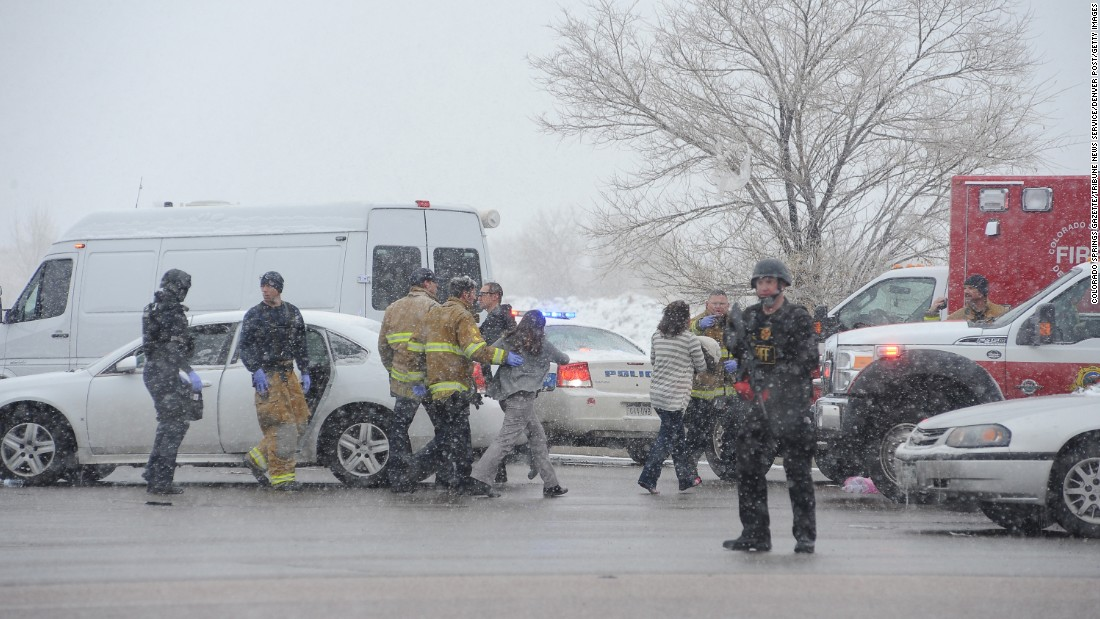 A woman is escorted to an ambulance by police near the scene.