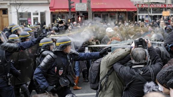 Police fight with activists during a protest ahead of the 2015 Paris Climate Conference at the Place de la République.