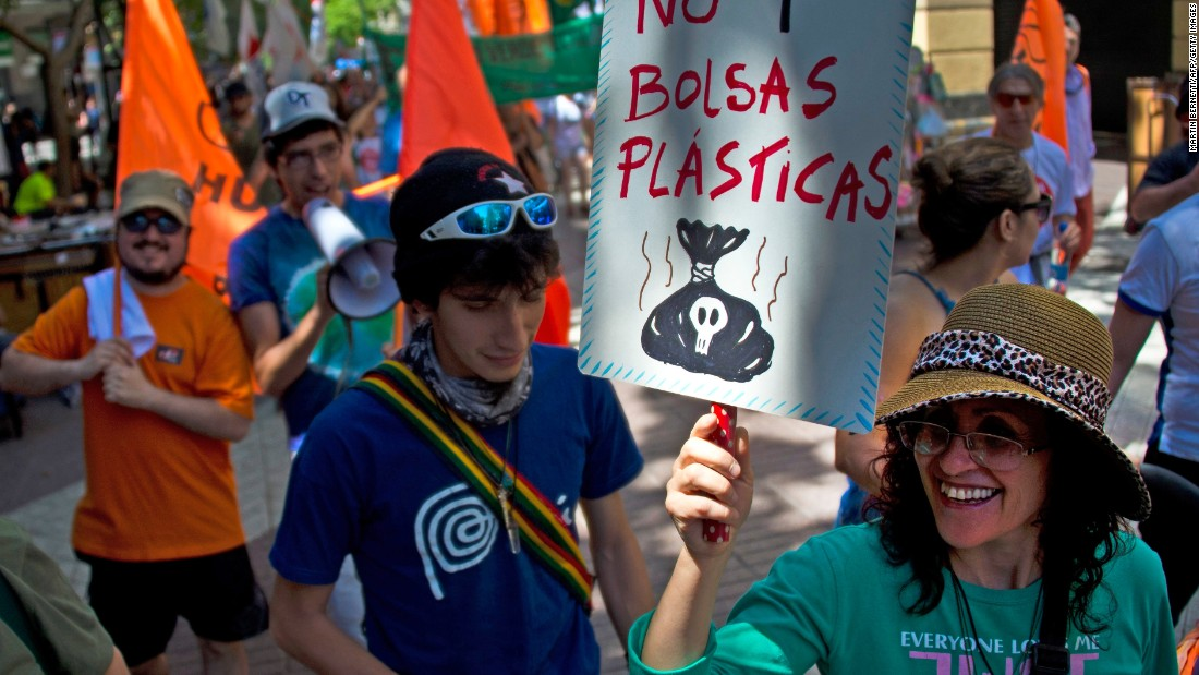 "A woman holds a sign reading ""No more plastic bags"" during a march in Santiago, Chile."