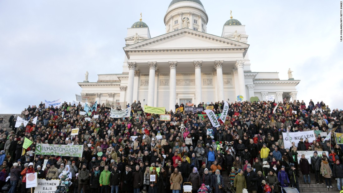 Climate march participants gather in front of the Helsinki Cathedral in Helsinki, Finland.