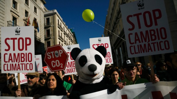 """A protester dressed as a panda bear marches with others holding banners reading """"stop climate change"""" through the streets of central Madrid, Spain."""