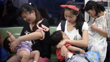 Mothers breastfeed their babies in a Beijing subway during an event celeberating the World Breastfeeding Week on August 1, 2015.