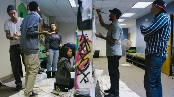"Timm, right, watches TRUE Skool students paint on a makeshift graffiti wall. Sarah Dollhausen, the program's founder and executive director, said, ""We hear from a lot of our young people, 'I'm just happy to be alive.' """