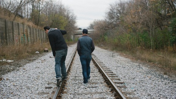 Graffiti artist Trevor Timm, right, walks with a friend along train tracks on the north side of the city, toward a bridge where Timm often paints.