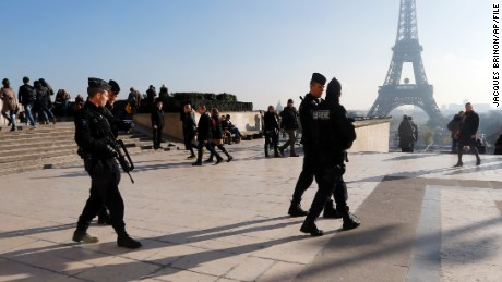French police officers patrol near the Eiffel Tower, in Paris, Monday Nov. 23, 2015.  French President Francois Hollande will preside over a national ceremony on Nov. 27 honoring the at least 130 victims of the deadliest attacks on France in decades.  (AP Photo/Jacques Brinon)