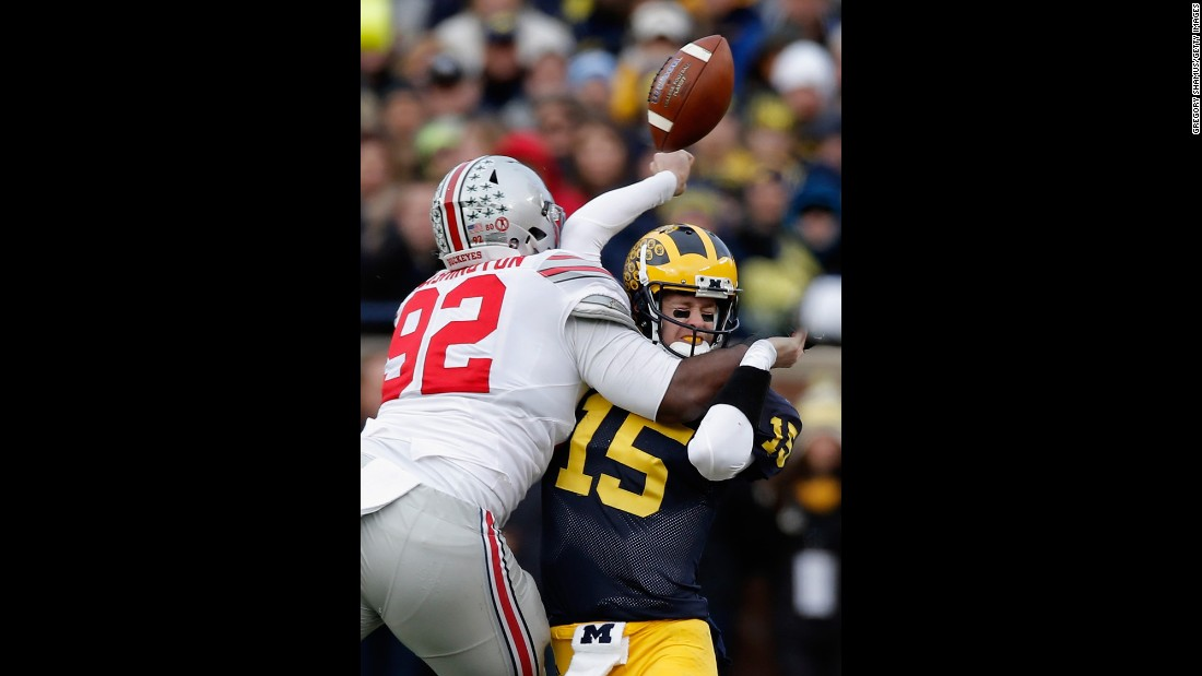 Michigan quarterback Jake Rudock fumbles the ball as he's hit by Ohio State's Adolphus Washington during a college football game played Saturday, November 28, in Ann Arbor, Michigan. Ohio State hammered its rival 42-13.