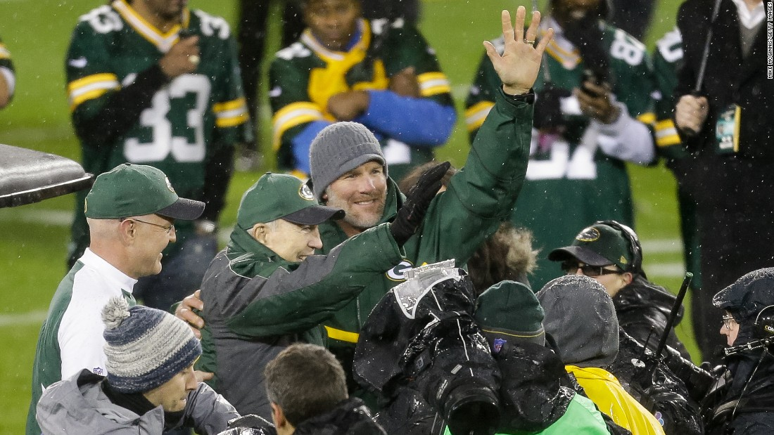 Former NFL quarterback Brett Favre, wearing the knit cap, waves to the crowd in Green Bay, Wisconsin, during his jersey retirement ceremony on Thursday, November 26. Waving with Favre is fellow Packers great Bart Starr.