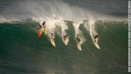 Six surfers drop into a wave during pre-contest surfing at the Eddie Aikau Big-Wave Invitational in 2009.