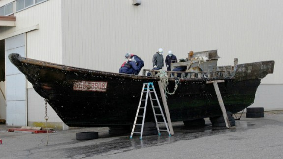 This picture taken on November 24, 2015 shows coast guard officials investigating a wooden boat at the Fukui port in Sakai city in Fukui prefecture, western Japan after the ship was found drifting off the coast of Fukui. Japan is investigating nearly a dozen suspicious boats recently found drifting off the country